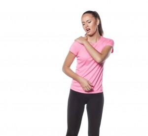 beautiful young sportswoman has a pain in her shoulder