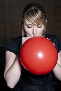 frau blst einen roten luftballon auf